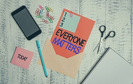 Conceptual hand writing showing Everyone Matters. Concept meaning all the showing have right to get dignity and respect Envelope sheet smartphone pen notepad clips wooden back