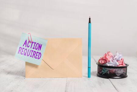 Writing note showing Action Required. Business concept for Regard an action from someone by virtue of their position Envelope sticky note marker paper balls container wooden background