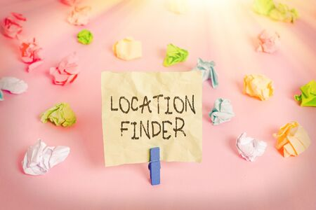 Conceptual hand writing showing Location Finder. Concept meaning A service featured to find the address of a selected place Colored crumpled papers empty reminder pink floor clothespin