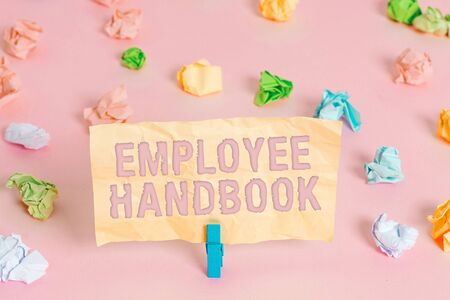 Writing note showing Employee Handbook. Business concept for Document that contains an operating procedures of company Colored crumpled papers empty reminder pink floor background clothespin