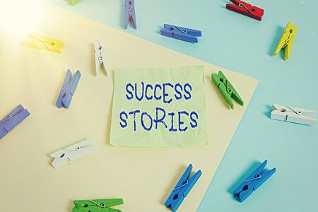 Writing note showing Success Stories. Business concept for life of rule models from how he started to his death Colored clothespin paper reminder with yellow blue background