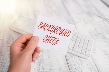 Word writing text Background Check. Business photo showcasing way to discover issues that could affect your business man holding colorful reminder square shaped paper white keyboard wood floor