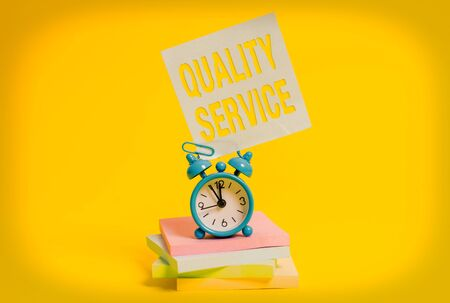 Word writing text Quality Service. Business photo showcasing how well delivered service conforms to client expectations Metal alarm clock blank sticky note stacked notepads colored background