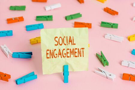 Conceptual hand writing showing Social Engagement. Concept meaning Degree of engagement in an online community or society Colored clothespin papers empty reminder pink floor office pin