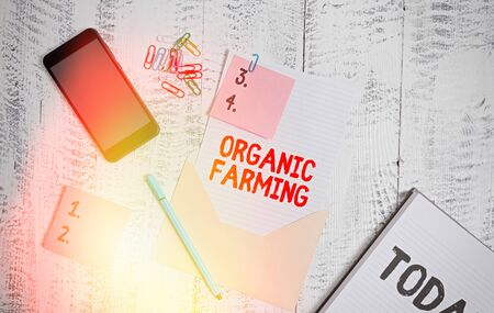 Handwriting text Organic Farming. Conceptual photo an integrated farming system that strives for sustainability Envelope sheet smartphone sticky notes pen notepad clips wooden background