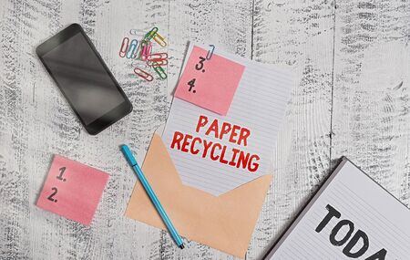 Handwriting text Paper Recycling. Conceptual photo Using the waste papers in a new way by recycling them Envelope sheet smartphone sticky notes pen notepad clips wooden background Standard-Bild