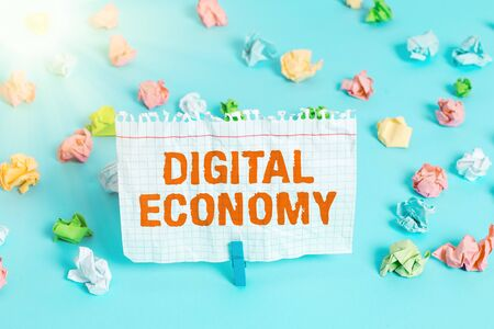 Text sign showing Digital Economy. Business photo showcasing worldwide network of economic activities and technologies Colored crumpled papers empty reminder blue floor background clothespin