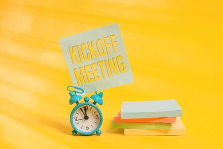 Handwriting text writing Kickoff Meeting. Conceptual photo Special discussion on the legalities involved in the project Metal alarm clock blank sticky note stacked notepads colored background