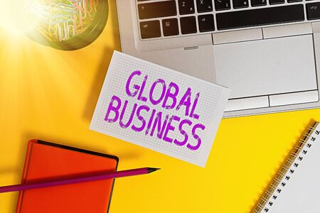 Text sign showing Global Business. Business photo showcasing Trade and business system a company doing across the world Laptop pencil sheet clips container spiral notebook colored background