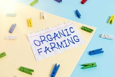 Word writing text Organic Farming. Business photo showcasing an integrated farming system that strives for sustainability Colored clothespin paper empty reminder yellow blue floor background office