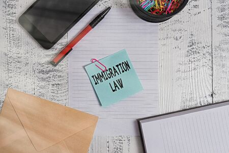 Text sign showing Immigration Law. Business photo showcasing Emigration of a citizen shall be lawful in making of travel Smartphone sheet clips ballpoint notebook envelope note wooden background