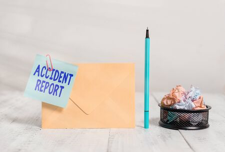 Writing note showing Accident Report. Business concept for A form that is filled out record details of an unusual event Envelope sticky note marker paper balls container wooden background