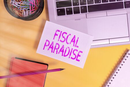 Text sign showing Fiscal Paradise. Business photo showcasing The waste of public money is a great concern topic Laptop pencil sheet clips container spiral notebook colored background