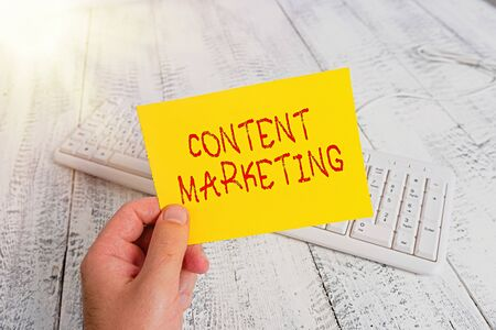Conceptual hand writing showing Content Marketing. Concept meaning Involves the creation and sharing of online material Man holding colorful reminder square shaped paper wood floor