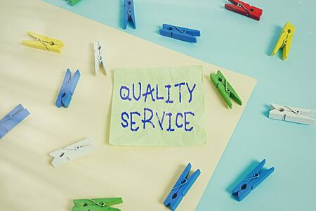 Writing note showing Quality Service. Business concept for how well delivered service conforms to client expectations Colored clothespin paper reminder with yellow blue background