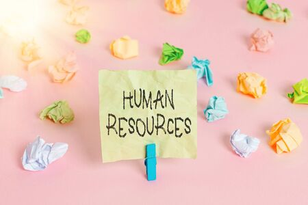 Conceptual hand writing showing Human Resources. Concept meaning The showing who make up the workforce of an organization Colored crumpled papers empty reminder pink floor clothespin