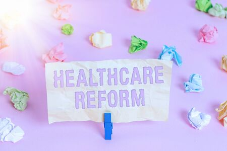 Writing note showing Healthcare Reform. Business concept for Innovation and Improvement in the quality of care program Colored crumpled papers empty reminder pink floor background clothespin