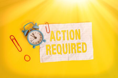 Writing note showing Action Required. Business concept for Regard an action from someone by virtue of their position Metal alarm clock blank crushed note rubber band colored background