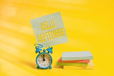 Handwriting text writing Hello September. Conceptual photo Eagerly wanting a warm welcome to the month of September Metal alarm clock blank sticky note stacked notepads colored background