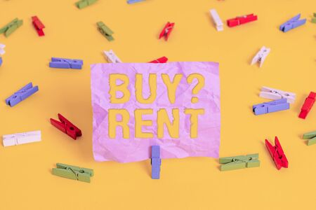 Word writing text Buy Question Rent. Business photo showcasing Group that gives information about renting houses Colored clothespin papers empty reminder yellow floor background office