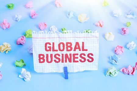 Text sign showing Global Business. Business photo showcasing Trade and business system a company doing across the world Colored crumpled papers empty reminder blue floor background clothespin