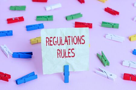Conceptual hand writing showing Regulations Rules. Concept meaning Standard Statement Procedure govern to control a conduct Colored clothespin papers empty reminder pink floor office pin Stok Fotoğraf