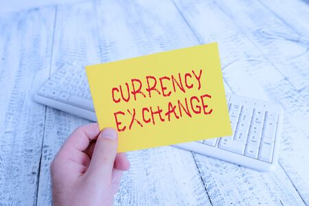 Conceptual hand writing showing Currency Exchange. Concept meaning Process of changing one currency into another ForEx Man holding colorful reminder square shaped paper wood floor