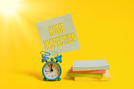 Handwriting text writing Home Inspection. Conceptual photo Examination of the condition of a home related property Metal alarm clock blank sticky note stacked notepads colored background