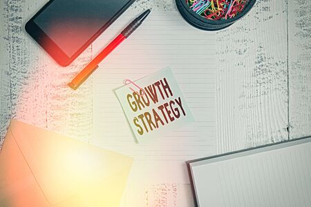 Text sign showing Growth Strategy. Business photo showcasing Strategy aimed at winning larger market share in shortterm Smartphone sheet clips ballpoint notebook envelope note wooden background