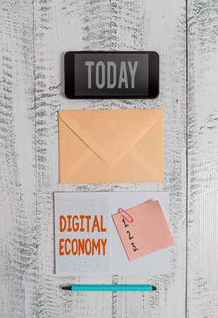 Word writing text Digital Economy. Business photo showcasing worldwide network of economic activities and technologies Envelop smartphone notepad note clip marker old wooden vintage background