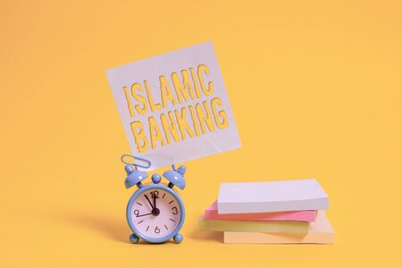 Handwriting text writing Islamic Banking. Conceptual photo Banking system based on the principles of Islamic law Metal alarm clock blank sticky note stacked notepads colored background Stockfoto