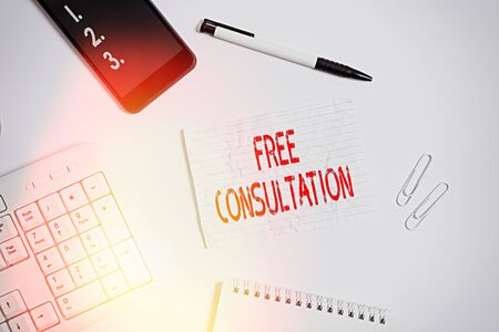 Writing note showing Free Consultation. Business concept for Giving medical and legal discussions without pay Flat lay above computer mobile phone pencil and copy space note paper