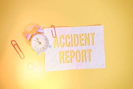 Writing note showing Accident Report. Business concept for A form that is filled out record details of an unusual event Metal alarm clock blank crushed note rubber band colored background