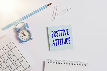Conceptual hand writing showing Positive Attitude. Concept meaning Being optimistic in Life Looking for good things Copy space on empty note paper with clock and pencil on the table