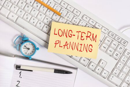 Text sign showing Long Term Planning. Business photo text Establish Expected Goals five or more years ahead Flat lay above empty note paper on the pc keyboard pencils and clock