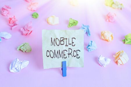 Conceptual hand writing showing Mobile Commerce. Concept meaning Using mobile phone to conduct commercial transactions online Colored crumpled papers empty reminder pink floor clothespin