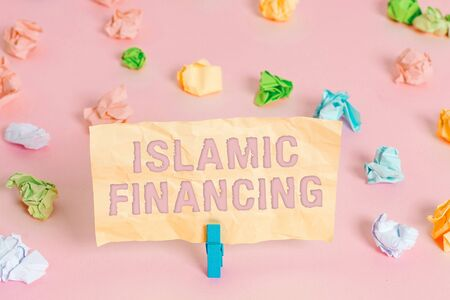 Writing note showing Islamic Financing. Business concept for Banking activity and investment that complies with sharia Colored crumpled papers empty reminder pink floor background clothespin