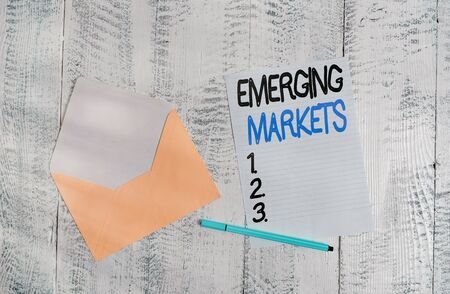 Text sign showing Emerging Markets. Business photo showcasing country that has some characteristics of developed stores Open colored envelope blank sheet letter paper ballpoint wooden background