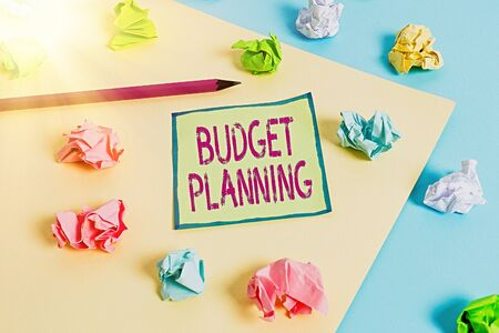 Conceptual hand writing showing Budget Planning. Concept meaning The written description about current and future expenses Colored crumpled paper empty reminder blue yellow clothespin