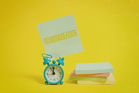 Handwriting text writing Groundbreaking. Conceptual photo Very new and a big change from other things of its type Metal alarm clock blank sticky note stacked notepads colored background