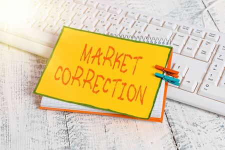 Writing note showing Market Correction. Business concept for When prices fall 10 percent from the 52 week high notebook reminder clothespin with pinned sheet light wooden