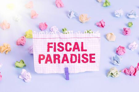 Text sign showing Fiscal Paradise. Business photo showcasing The waste of public money is a great concern topic Colored crumpled papers empty reminder blue floor background clothespin