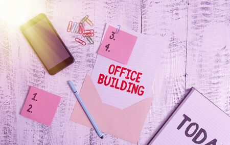 Handwriting text Office Building. Conceptual photo Commercial buildings are used for commercial purposes Envelope sheet smartphone sticky notes pen notepad clips wooden background