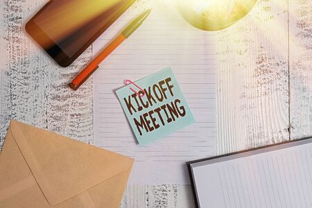Text sign showing Kickoff Meeting. Business photo showcasing Special discussion on the legalities involved in the project Smartphone sheet clips ballpoint notebook envelope note wooden background