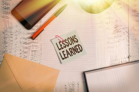 Text sign showing Lessons Learned. Business photo showcasing Promote share and use knowledge derived from experience Smartphone sheet clips ballpoint notebook envelope note wooden background