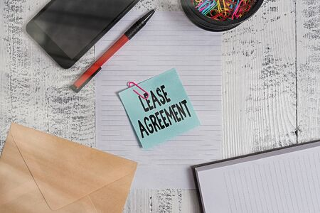 Text sign showing Lease Agreement. Business photo showcasing Contract on the terms to one party agrees rent property Smartphone sheet clips ballpoint notebook envelope note wooden background