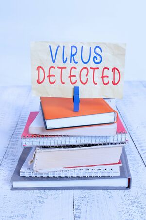 Text sign showing Virus Detected. Business photo text A computer program used to prevent and remove malware pile stacked books notebook pin clothespin colored reminder white wooden