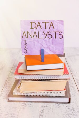 Handwriting text Data Analysts. Conceptual photo Programmer Design and Create Report Identifies patterns pile stacked books notebook pin clothespin colored reminder white wooden