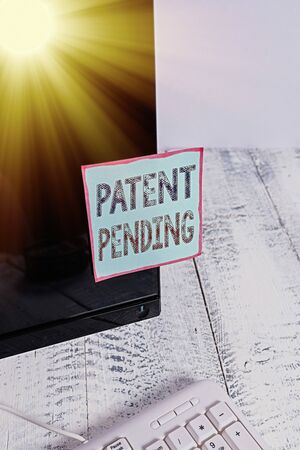 Text sign showing Patent Pending. Business photo showcasing Request already filed but not yet granted Pursuing protection Notation paper taped to black computer monitor screen near white keyboard