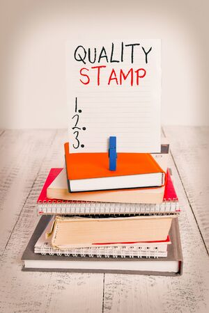 Word writing text Quality Stamp. Business photo showcasing Seal of Approval Good Impression Qualified Passed Inspection pile stacked books notebook pin clothespin colored reminder white wooden